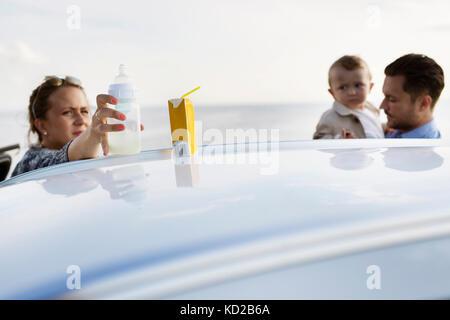 Los padres con hijos (18-23 meses) detrás de coches Imagen De Stock