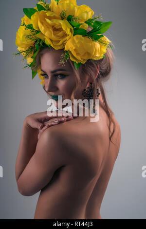 Retrato de moda de la parte de atrás de una chica sexy con maquillaje brillante y una corona de flores de colores brillantes Imagen De Stock