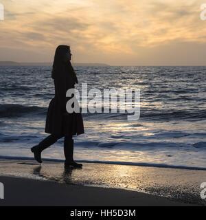 Una mujer está caminando por la playa al atardecer. Imagen De Stock