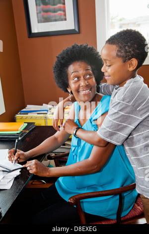 Mujer trabajando en su oficina doméstica con hijo Imagen De Stock