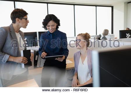 Empresarias sonriente con digital comprimido en armario de oficina Imagen De Stock