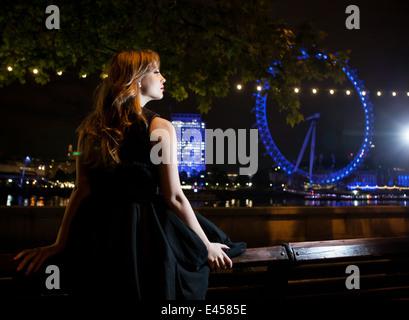 Mujer joven mirando a Ojo de Londres por la noche, Londres, Reino Unido. Imagen De Stock