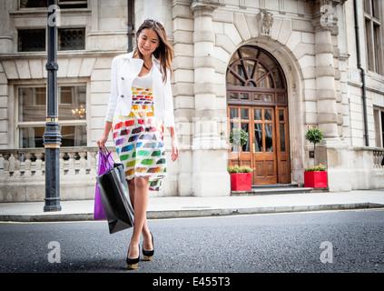 Mujer joven caminando en la calle de Londres, llevando bolsas de la compra. Imagen De Stock