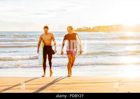 Surfistas masculinos llevar tablas de surf en la soleada playa. Imagen De Stock