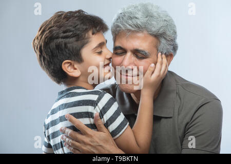 Nieto besando a su abuelo Imagen De Stock