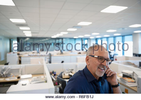Sonriente empresario senior hablando por teléfono móvil en la oficina abierta Imagen De Stock