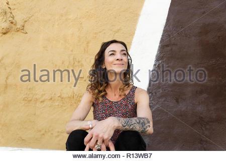 Retrato de una mujer sonriente sentada contra una pared en España Imagen De Stock