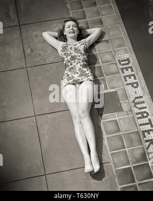 1940 morena sonriente mujer vistiendo un traje de baño pieza mentir por extremo profundo de una piscina mirando a la Cámara - s9593 HAR001 HARS ATHLETIC CONFIANZA B&W contacto ocular morena felicidad alegre poniendo un alto ángulo de esparcimiento por parte de sonrisas alegres elegante traje de baño cooperación mujer adulta joven EN BLANCO Y NEGRO la etnia CAUCÁSICA HAR001 UNA PIEZA ANTIGUA Imagen De Stock