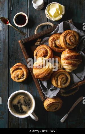 Variedad de bollos de hojaldre casera rollos de canela y croissant servido con taza de café, mermelada, mantequilla como desayuno sobre tablones de madera oscura de fondo. Imagen De Stock