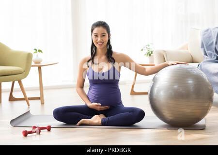Alegre mujer embarazada ejercicio en el hogar Imagen De Stock