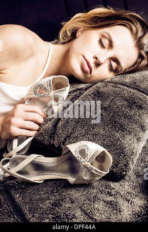 Mujer sosteniendo los zapatos en la cama Imagen De Stock