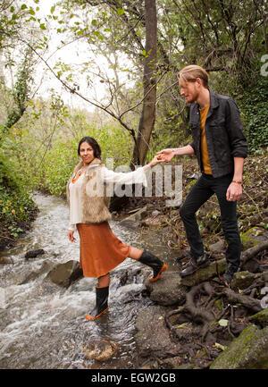 Mujer ayudando al hombre a través de Creek. Imagen De Stock