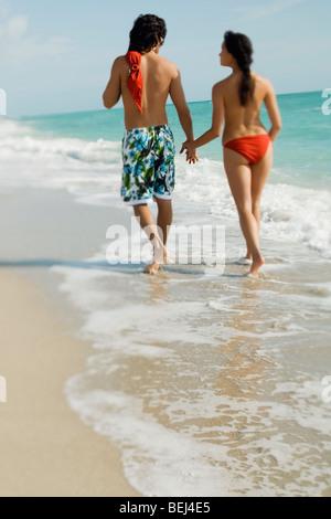 Vista trasera de una pareja joven, caminar en la playa Imagen De Stock