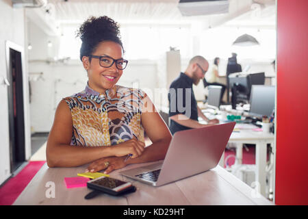 Mujer sonriente con laptop, compañeros de trabajo en segundo plano. Imagen De Stock