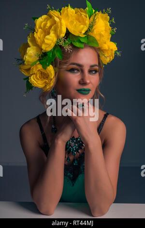 Retrato de una bonita rubia con un aro de flores amarillas y maquillaje brillante sobre un fondo oscuro Imagen De Stock
