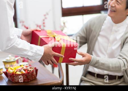 Hijo dando don a su padre durante el Año Nuevo Chino Imagen De Stock