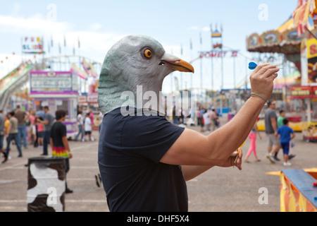 Persona llevaba una máscara de la paloma tiene un dardo en un Estado justo. Imagen De Stock