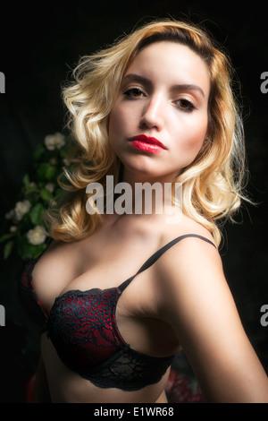 Una joven, bella y sexy mujer rubia en un sujetador de encaje rojo seductivly mirando a la cámara. Imagen De Stock