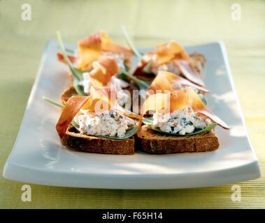Queso fresco y jamón de Bayona crostinis Imagen De Stock