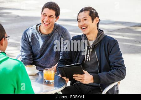 Amigos varones con tableta digital riendo de café en la acera Imagen De Stock