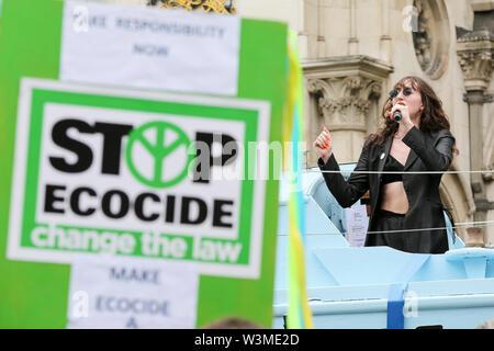 Jessica Winter canta en un barco real situado fuera de los tribunales de justicia durante la protesta.Cientos de extinción rebelión activistas contra el cambio climático protestas fuera de las Cortes Reales de justicia exigiendo el sistema legal para asumir la responsabilidad en la crisis del cambio climático, y garantizar la seguridad de las generaciones futuras, haciendo el ecocidio derecho. El grupo ecologista está organizando protestas similares en Leeds, Cardiff, Glasgow, Bristol, Norwich y otras ciudades de todo el país. Imagen De Stock