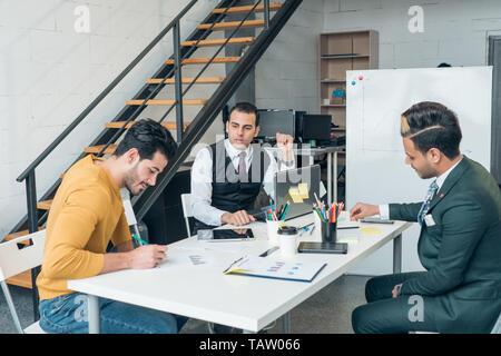 La comunicación empresarial entre los jóvenes empresarios en una oficina moderna. Las negociaciones internacionales. Imagen De Stock