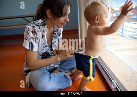 Madre hispana inspecciona el interior de su pañal del niño para ver si se necesita el cambio. Imagen De Stock