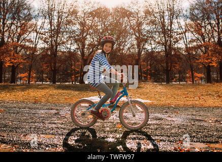 Chica sonriente montar en bicicleta en el parque, Estados Unidos Imagen De Stock