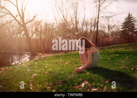 Chica sentada sobre la hierba, Estados Unidos Imagen De Stock