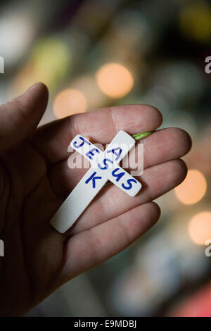 Persona que ostente cruz pequeña con el texto 'pedirle a Jesús Imagen De Stock