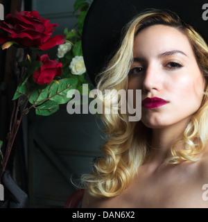 Close-up retrato de una joven muy bella mujer rubia posando con rosas rojas. Imagen De Stock