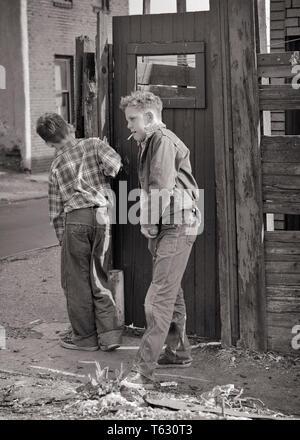 1950 dos chicos adolescentes vestidos ásperos lleva vaqueros fumar cigarrillos ESCONDIDOS EN EL MIRADOR DEL BARRIO DE TUGURIOS BACK ALLEY - w59 HAR001 HARS AMISTAD PERSONAS DE LONGITUD COMPLETA MASCULINO ADOLESCENTE ÁSPERO DENIM B&W TRISTEZA CIGARRILLOS LIBERTAD BARRIO AVENTURA EN penurias adolescente delincuente blue jeans juveniles pre-adolescentes pre-teen BOY TUGURIO COMPAÑERISMO TRUANT UNSUPERVISED BLANCO Y NEGRO la etnia CAUCÁSICA HAR001 NECESITADOS ANTICUADO Imagen De Stock