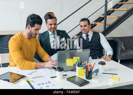 Los jóvenes vean en el portátil. Los periodistas están preparando un nuevo artículo o proyecto. Imagen De Stock