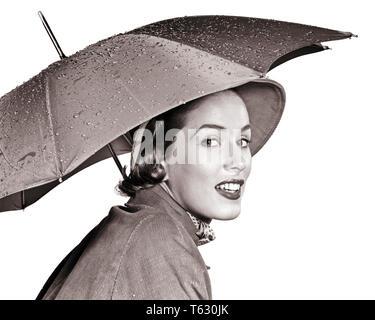 1950 MUJER sonriente mirando a la cámara bajo un paraguas llevar impermeable y sombrero - S381 HAR001 HARS PERSONAS LLOVIENDO CONFIANZA B&W contacto ocular bastante cosméticos de cabeza y hombros estilos y modas elegantes mujer adulta joven EN BLANCO Y NEGRO la etnia CAUCÁSICA HAR001 ANTICUADO Imagen De Stock