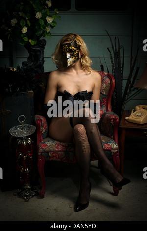 Mujer rubia en bauta máscara veneciana, tacones y medias panty, implícita con la mano desnuda cubriendo Imagen De Stock