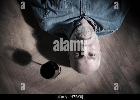 Viejo hombre descansando en el piso con copa de vino en el lateral. Imagen conceptual de la soledad y la jubilación. Imagen De Stock