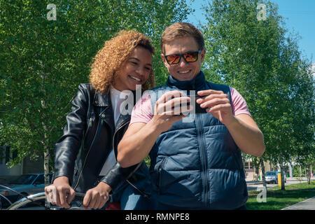 Chico y chica mira las fotos en el teléfono y reír fuera en la primavera Imagen De Stock