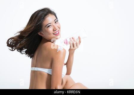 Hermosa joven aplicar bloqueador solar Imagen De Stock