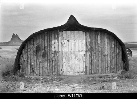 Isla Santa Northumberland, tradicional de pescadores de hangar realizada a partir de un viejo barco de Pucherito de arenque, Castillo de Lindisfarne en el horizonte 1971, 1970 en el Reino Unido. HOMER SYKES Imagen De Stock