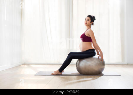Alegre mujer embarazada sentada sobre la bola de fitness Imagen De Stock