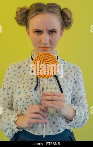 Retrato de una divertida Chica sujetando una piruleta naranja en la parte delantera de la cara sobre fondo brillante Imagen De Stock