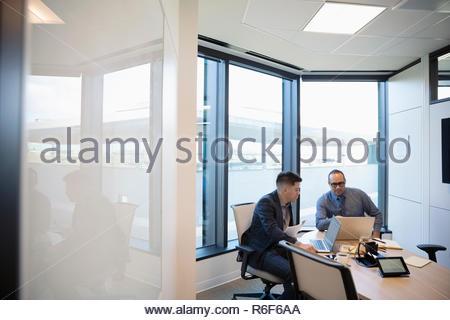 Los empresarios que trabajan en equipos portátiles en la sala reunión Imagen De Stock