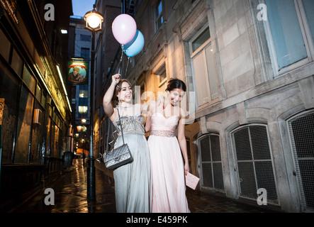Dos amigas en trajes de noche tras noche de fiesta en la ciudad Imagen De Stock
