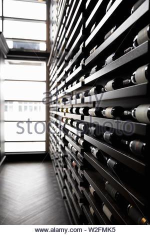 Las botellas de vino en una fila de racks en wine bar Imagen De Stock