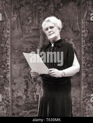 1930 elegante mujer vistiendo senior vestido de terciopelo sujetando el papel de DAR UN DISCURSO ANTE UN TAPIZ mirando a la Cámara - s8265 HAR001 HARS longitud media estimadas personas expresiones ADULTO SENIOR B&W CONTACTO OCULAR ALTOS MUJER ANTES OLDSTERS DODO LA RIQUEZA Un vocero de ancianos TAPIZ RESPONSABILIDAD DELANTE DE INTERROGATORIO EN BLANCO Y NEGRO la etnia CAUCÁSICA HAR001 IMPERIOSA ANTICUADO Imagen De Stock