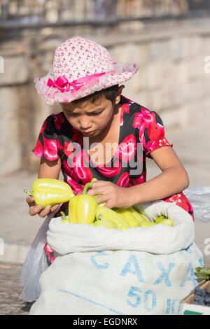 Niña vendiendo pimientos Samarcanda mercado, Provincia Samarqand, Uzbekistán Imagen De Stock