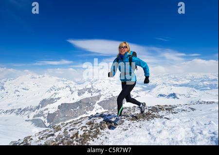 La mujer disfruta de una carrera a través de una cordillera Alpes nevados. Imagen De Stock