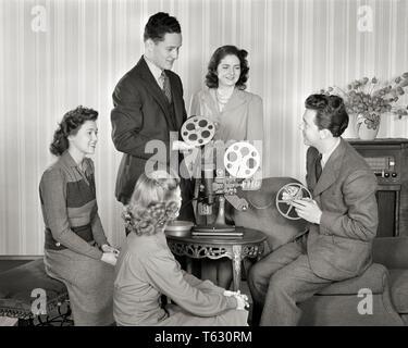 1940 Un grupo de hombres y mujeres jóvenes sonriendo con rollos de película CONFIGURAR EL PROYECTOR DE CINE EN CASA - u591 HAR001 HARS OLD FASHION estilo juvenil Comunicación adulto joven relajado estilo de vida 5 Mujeres 5 HOME VIDA AMISTAD DE LONGITUD COMPLETA longitud media estimadas PERSONAS VARONES ADOLESCENTE ADOLESCENTE ENTRETENIMIENTO ACTIVIDAD HABILIDADES B&W Proyector de diversiones HOBBY OCIO Y aficiones de interés conocimiento pasatiempo recreativo PLACER DE ELEGANTE CONCEPTUAL menores adolescente tambores relajación compañerismo adulto joven hombre mujer adulta joven amateur EN BLANCO Y NEGRO la etnia CAUCÁSICA GOCE HAR001 ANTICUADO Imagen De Stock