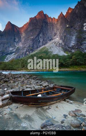 Row-barco junto al río Rauma. En el fondo es el troll de pared vertical de 3000 pies y los picos Trolltindane, Romsdalen valle, Noruega. Imagen De Stock