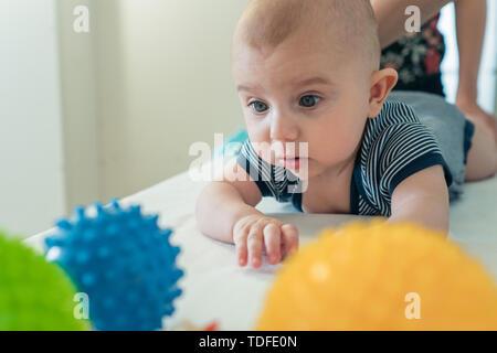 Un pequeño niño lindo cuidadosamente elige una pelota de goma de diferentes colores. El desarrollo del niño. El crecimiento de los niños Imagen De Stock